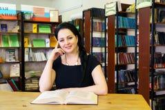 Libro della tenuta della donna che posa per la macchina fotografica alla biblioteca Immagine Stock Libera da Diritti