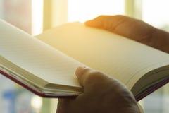 Libro della tenuta della mano nella stanza di vetro Fotografia Stock