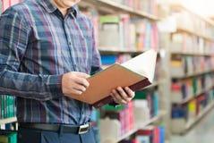 Libro della tenuta dello studente della mano e fondo delle biblioteche Immagini Stock