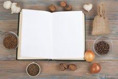 Libro dello spazio in bianco del cuoco di ricetta su fondo di legno, cucchiaio, matterello, tovaglia a quadretti Immagini Stock