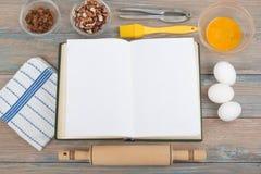 Libro dello spazio in bianco del cuoco di ricetta su fondo di legno, cucchiaio, matterello, tovaglia a quadretti Fotografie Stock Libere da Diritti