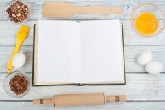 Libro dello spazio in bianco del cuoco di ricetta su fondo di legno, cucchiaio, matterello, tovaglia a quadretti Vista superiore immagine stock libera da diritti