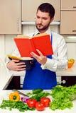 Libro di cucina bello della lettura del giovane attentamente Immagine Stock