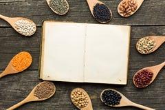 Libro di cucina in bianco e vari legumi Immagine Stock
