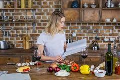 Libro di cucina biondo della tenuta della donna mentre preparando pizza in cucina fotografia stock libera da diritti