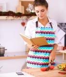 Libro di cucina della lettura della giovane donna nella cucina, cercante ricetta immagine stock libera da diritti