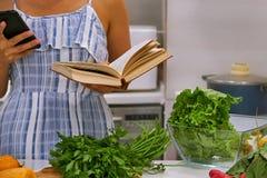 Libro di cucina della lettura della giovane donna nella cucina, cercante ricetta immagini stock libere da diritti