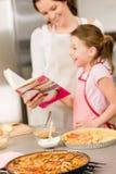 Libro di cucina di cottura di sguardo della figlia e della madre immagine stock libera da diritti