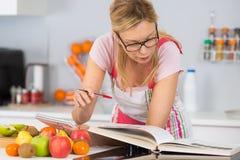 Libro di cucina maturo della lettura della donna in cucina che cerca ricetta fotografia stock