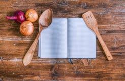 Libro di cucina sopra la tavola di legno con alcune cipolle fotografie stock libere da diritti