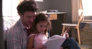 Libro di And Daughter Reading del padre nella camera da letto del bambino video d archivio
