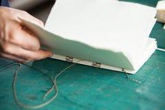 Libro di fabbricazione della mano sulla Tabella Immagini Stock