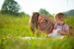 Libro di lettura abbastanza giovane della madre alla sua piccola figlia immagini stock