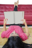 Libro di lettura abile dello studente sul tappeto Immagine Stock Libera da Diritti