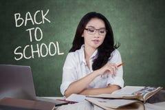 Libro di lettura adolescente asiatico dello studente nella classe Immagine Stock