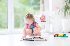 Libro di lettura adorabile della ragazza del bambino nella stanza soleggiata Immagine Stock
