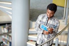 Libro di lettura africano del ragazzo o dell'uomo dello studente alla biblioteca Fotografia Stock Libera da Diritti