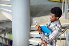 Libro di lettura africano del ragazzo o dell'uomo dello studente alla biblioteca Immagine Stock