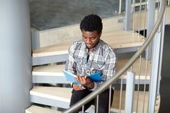 Libro di lettura africano del ragazzo o dell'uomo dello studente sulle scale Immagine Stock