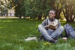 Libro di lettura afroamericano dello studente in città universitaria su erba Fotografia Stock