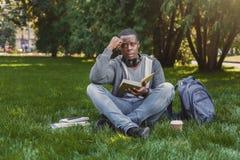 Libro di lettura afroamericano disperato dello studente in città universitaria su erba Fotografie Stock