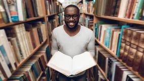 Libro di lettura afroamericano etnico del tipo, sorridente in navata laterale della biblioteca Immagine Stock
