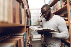 Libro di lettura afroamericano etnico del tipo, sorridente in navata laterale della biblioteca Fotografie Stock Libere da Diritti