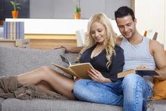 Libro di lettura amoroso delle coppie sul sofà Fotografia Stock
