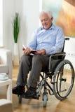 Libro di lettura anziano dell'uomo a casa Immagini Stock