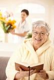 Libro di lettura anziano felice della donna Immagini Stock