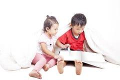 Libro di lettura asiatico dei fratelli germani Immagine Stock