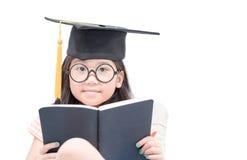 Libro di lettura asiatico felice del laureato del bambino della scuola con il cappuccio di graduazione Fotografia Stock