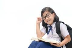 Libro di lettura asiatico sveglio degli occhiali di usura della ragazza Immagine Stock Libera da Diritti