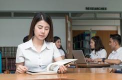 Libro di lettura asiatico sveglio dello studente nell'università delle biblioteche Fotografie Stock