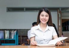 Libro di lettura asiatico sveglio dello studente nell'università delle biblioteche Immagine Stock