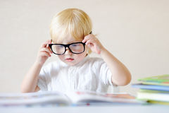 Libro di lettura astuto del ragazzino a casa Immagine Stock