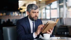 Libro di lettura astuto dell'imprenditore che si siede in caffè da solo che gode della storia interessante archivi video