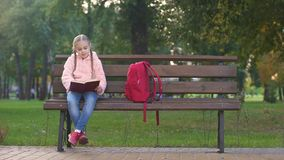 Libro di lettura astuto della ragazza in parco sul banco, hobby intellettuale, spendente tempo libero archivi video