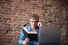 Libro di lettura astuto dello studioso del giovane, seduta con il computer portatile portatile in caffetteria Immagini Stock Libere da Diritti