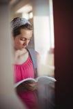 Libro di lettura attento della scolara in biblioteca Fotografia Stock Libera da Diritti