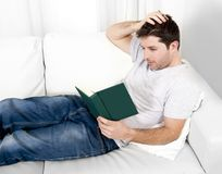 Libro di lettura attraente dell'uomo o studiare sullo strato Fotografia Stock