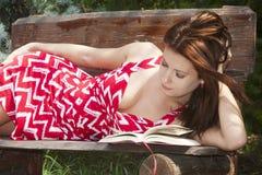 Libro di lettura attraente della donna nella sosta Immagine Stock