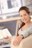 Libro di lettura attraente della ragazza sul sofà nel paese Immagini Stock
