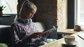 Libro di lettura attraente dello studente in pagine di giro del caffè che godono della storia interessante video d archivio