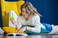 Libro di lettura biondo della donna a casa e mettendo sul pavimento accanto alla poltrona gialla fotografia stock