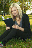 Libro di lettura biondo della ragazza dell'allievo Immagine Stock Libera da Diritti