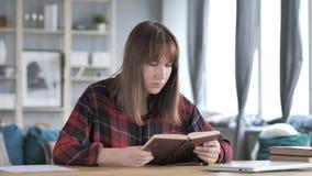 Libro di lettura casuale della ragazza in posto di lavoro creativo archivi video
