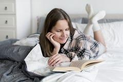 Libro di lettura caucasico della donna a letto Fotografia Stock