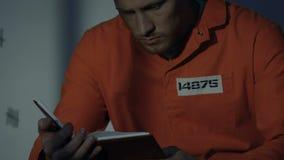 Libro di lettura caucasico solo del prigioniero in cellula, tempo libero in prigione, primo piano stock footage
