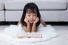Libro di lettura cinese asiatico sonnolento della bambina sul pavimento Fotografia Stock